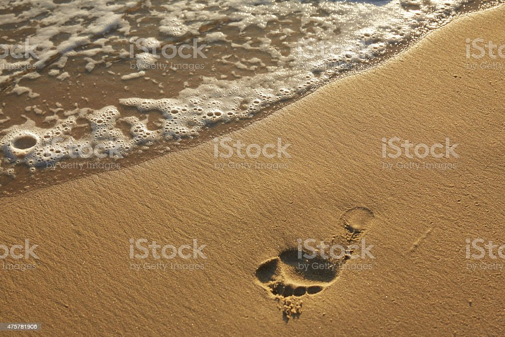 trace of a human foot on a sandy beach stock photo