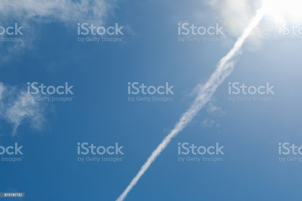 Trace of plane in the sky clouds. Abstract background. stock photo