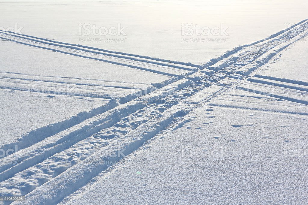 Traces from a snowmobile on a snow surface stock photo