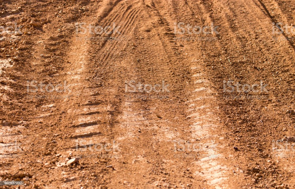 Traces from the car on the red clay soil stock photo