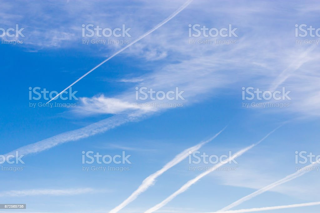 traces of an airplane on a blue sky stock photo