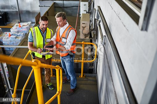 Shot of two warehouse workers standing on stairs discussing papework