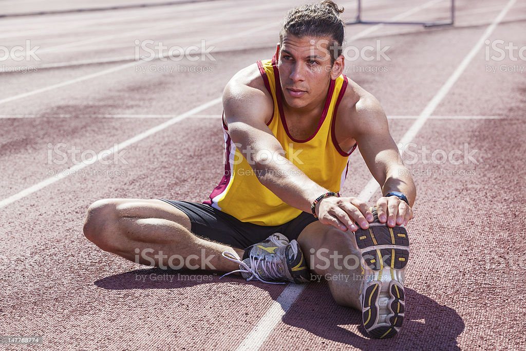 Track and Field Athlete Stretching Before the Race royalty-free stock photo