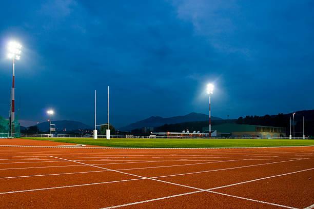 Track and Field Stadium at Night stock photo