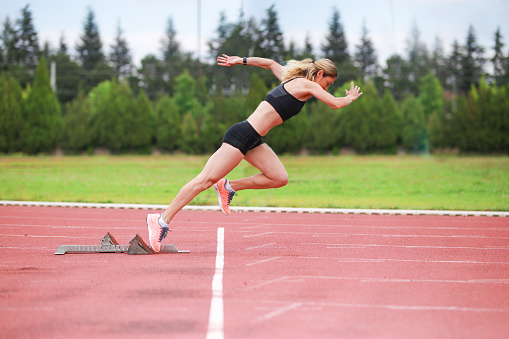 Track athlete exploding out of the starting blocks in stadium