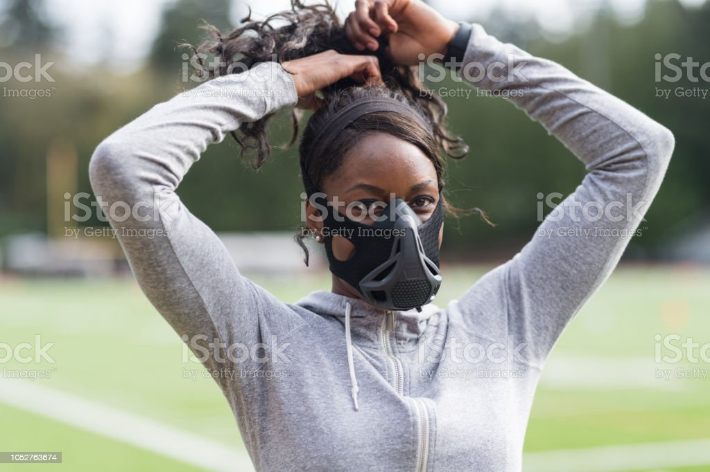 Track athlete using high altitude training mask stock photo