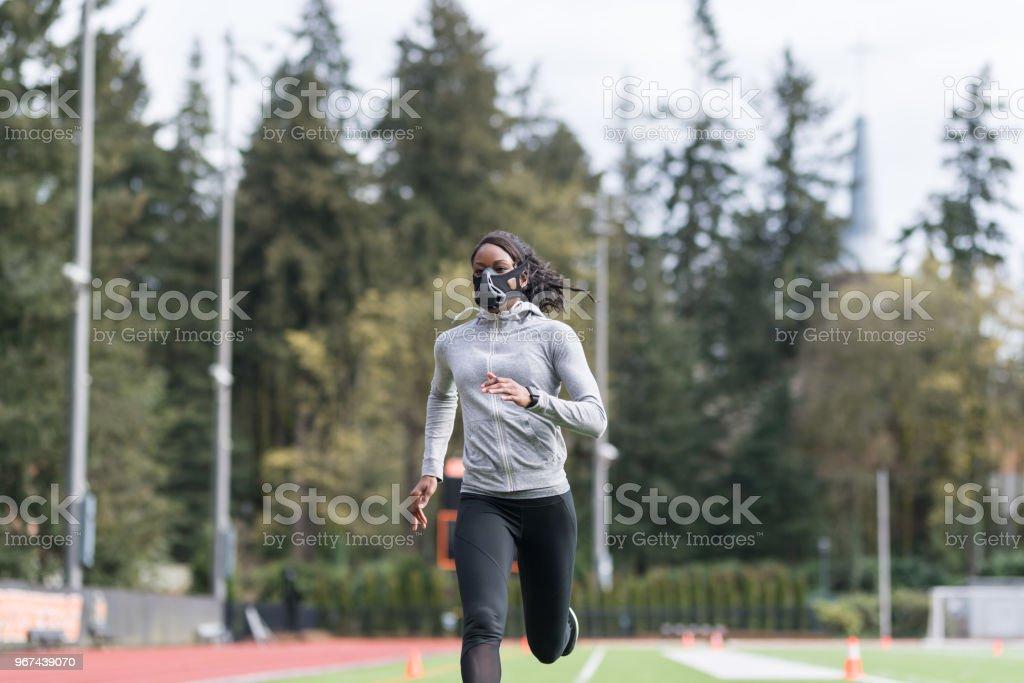 Track athlete using high altitude training mask stock photo