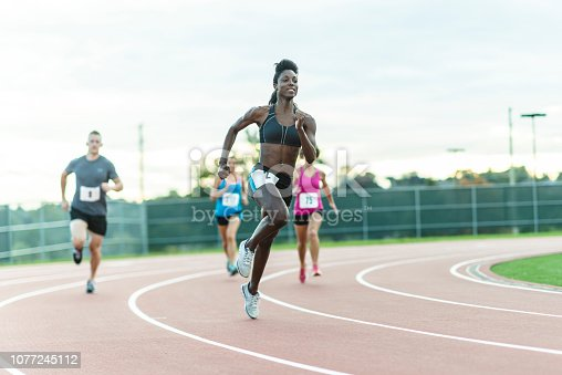 A diverse group of athletes competes in a race on an outdoor running track.