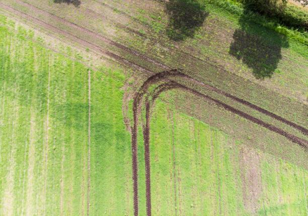 spur eines traktors auf ein feld, das eine wendung gemacht hat beim erreichen der feldgrenze abstrakte wirkung durch vertikale luftaufnahme, als hintergrund verwendet werden - aerial view soil germany stock-fotos und bilder