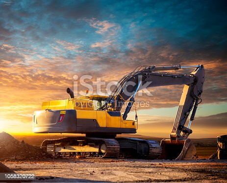 Excavator at a construction site against the setting sun. Excavator on the background of the setting sun. Huge excavator in the evening. Tracked excavator at the construction site in the evening.