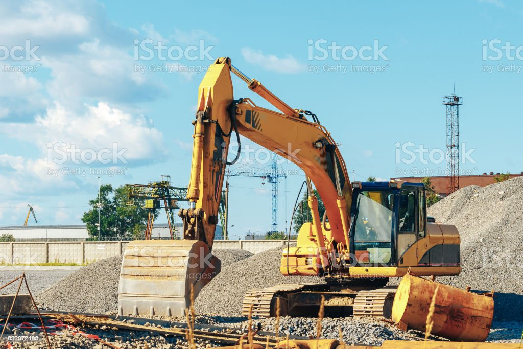 Tracked excavator on a construction site amid the pile of rubble stock photo