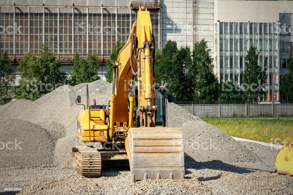 Tracked excavator on a construction site among piles of crushed stone stock photo