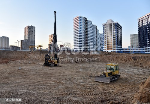 Tracked pile-driver and bulldozer at construction site on sunset. Piles driven into the ground by vibrating hydraulic hammer. Ground drilling machine. Drilling rig or vibrating hydraulic hammer
