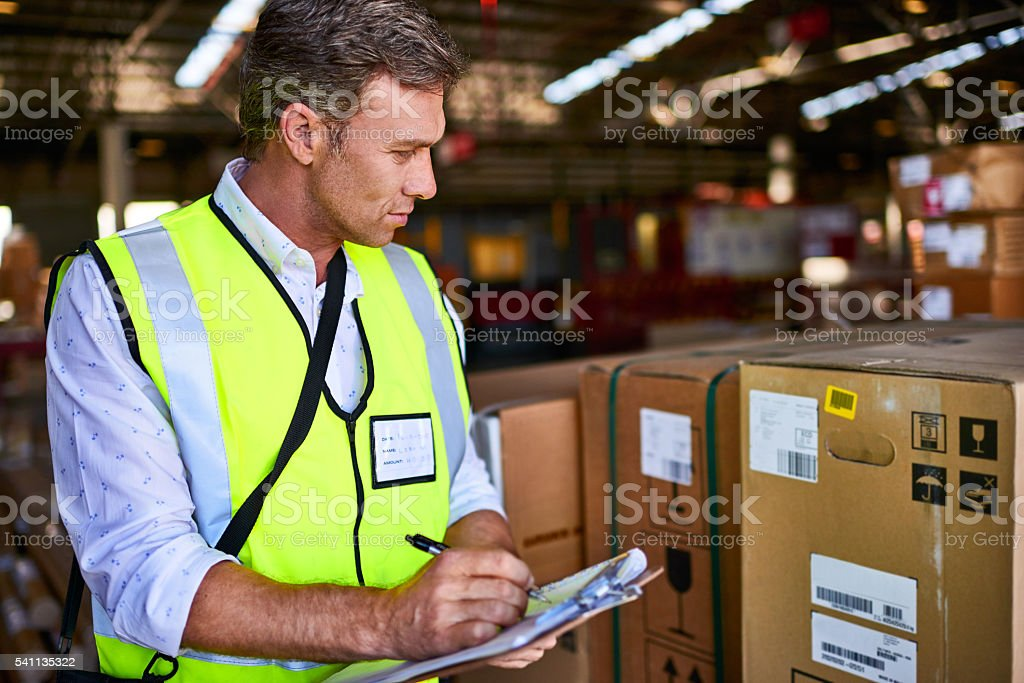 Shot of a warehouse worker standing in a large warehouse holding a...