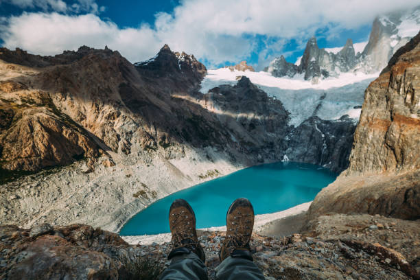 Tracking boots shoes on a blue lake background among mountains and cloudy sky stock photo