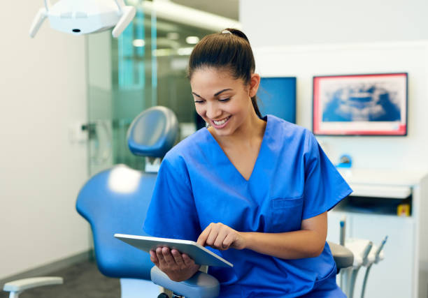 tracking her dental appointments for the day - dental assistant stock photos and pictures