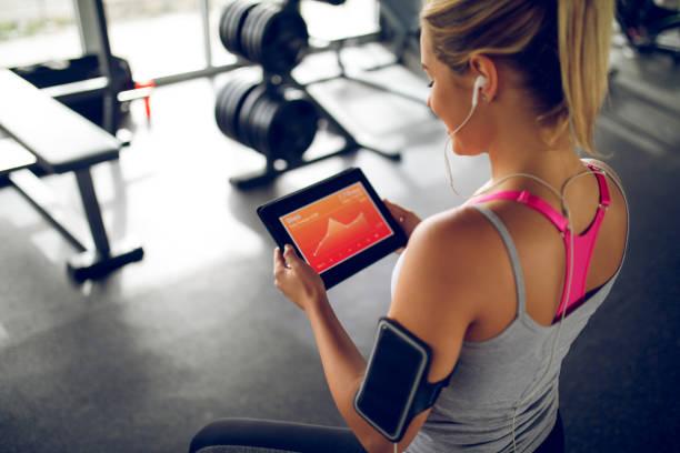 tracking ihre fortschritte mit fitness-app auf digital-tablette - trainingsplan frauen stock-fotos und bilder