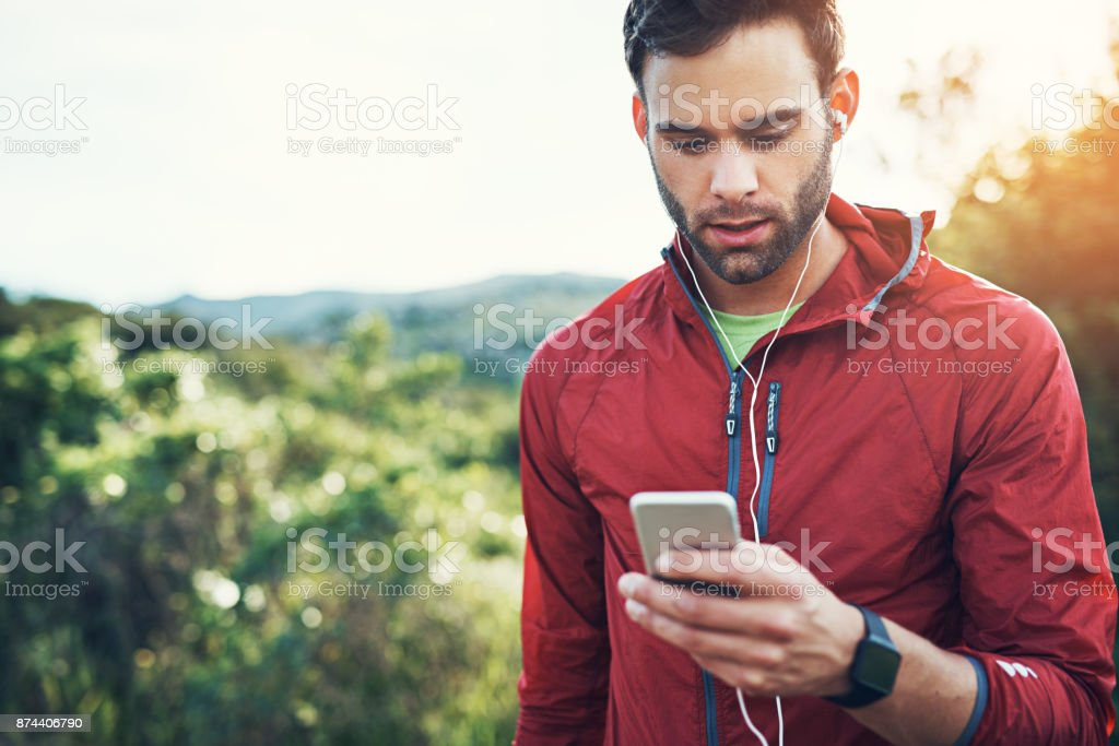 Tracking his route via GPS Cropped shot of a handsome young male athlete checking his messages while out for a morning run 20-29 Years Stock Photo