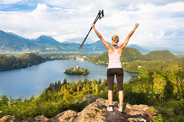 Tracking round Bled Lake in Julian Alps, Slovenia. Made it! Young spoty active lady with hiking sticks and hands rised admiring beautiful nature around Bled Lake in Julian Alps, Slovenia. nordic walking stock pictures, royalty-free photos & images