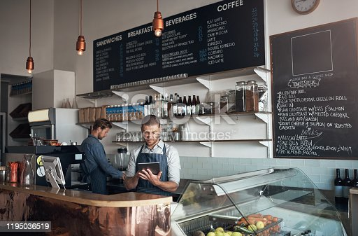 Shot of a mature man using a digital tablet while working alongside a colleague in a cafe