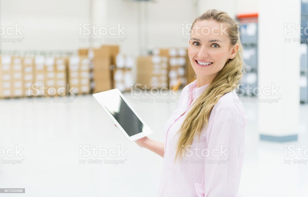 Horizontal color image of happy woman manager working in warehouse...