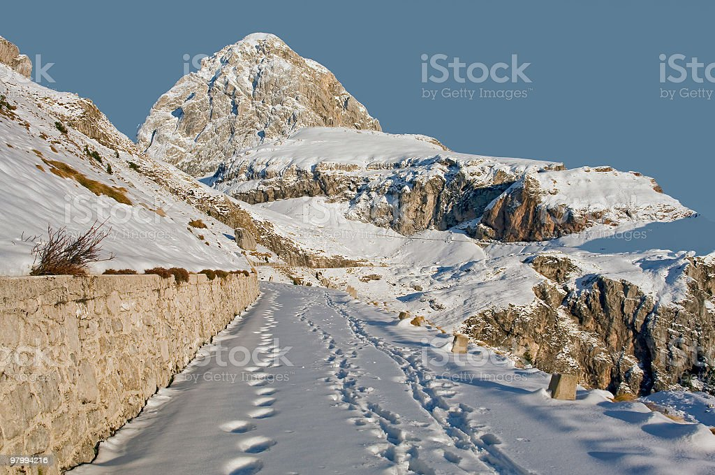 Tracks on Snowy Road High in Mountains royalty-free stock photo