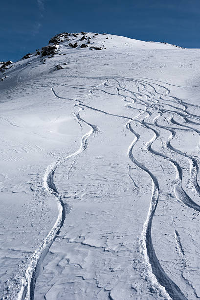 Tracks running down in the snow on the mountain slopes stock photo