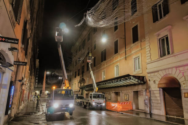 Tracks with workers install the festive illumination at Piazza del Popolo area. stock photo