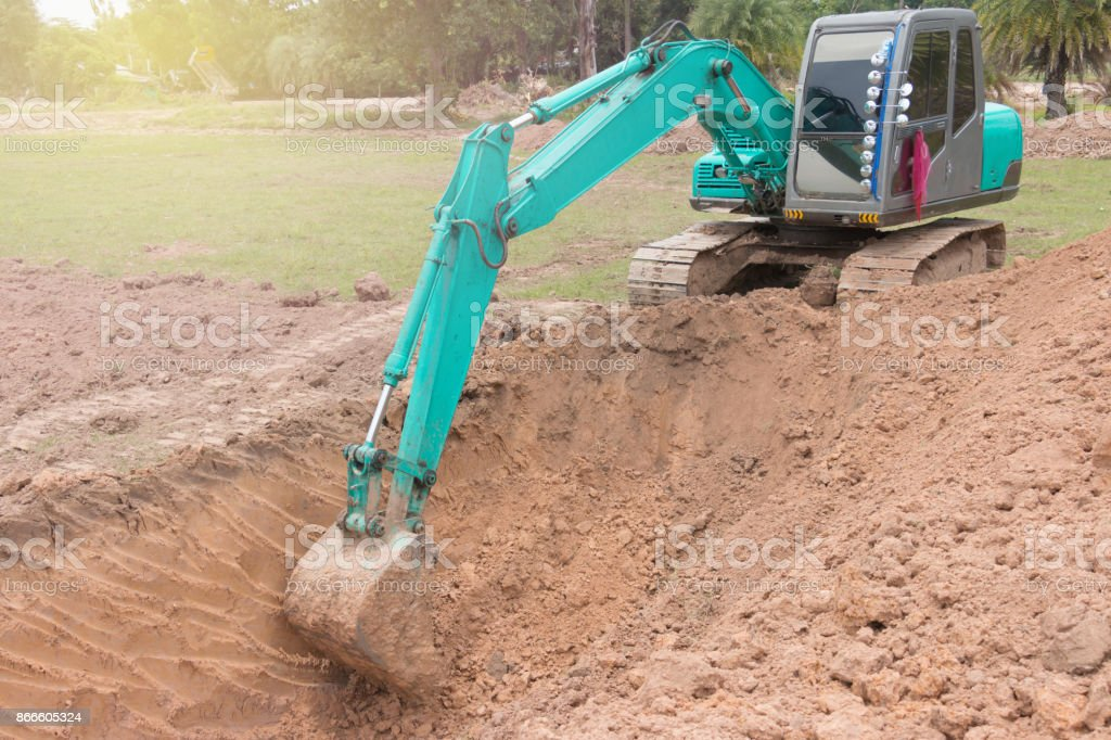 Track-type loader excavator machine doing earthmoving work at construction site stock photo