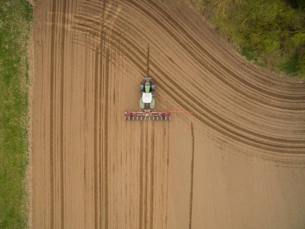 traktor - luftbild eines traktors bei der arbeit, die pflege eines feldes im frühling - aerial view soil germany stock-fotos und bilder