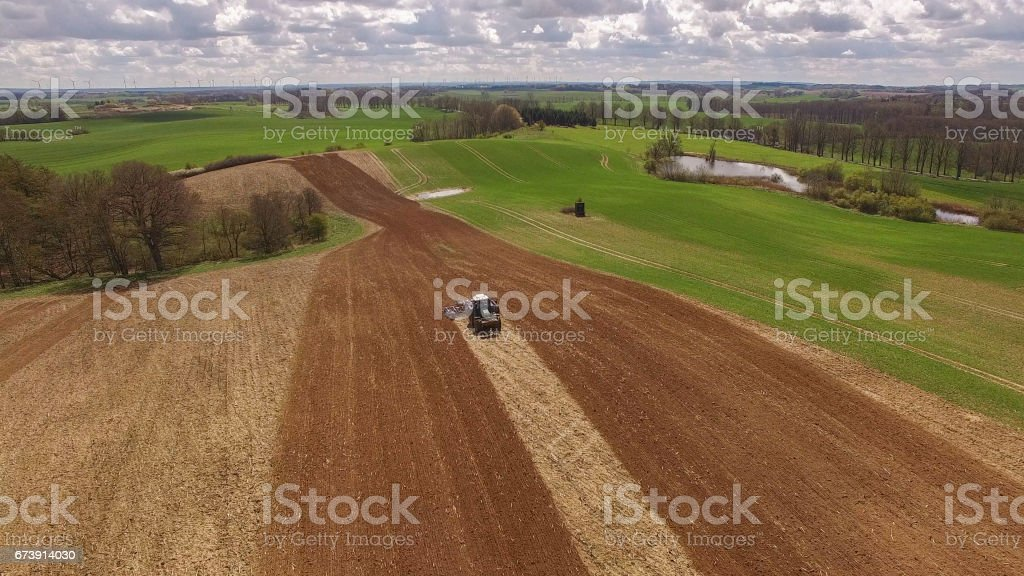 tractor - aerial view of a tractor at work - cultivating a field in spring with blue sky - agricultural machinery stock photo