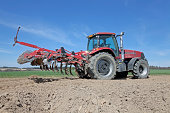 Tractor with cultivator on field.