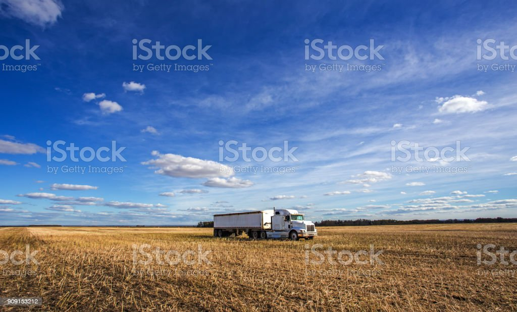 A tractor and trailer parked in harvested field stock photo