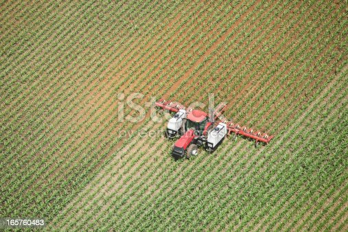 Aerial view of a tractor towing an applicator is spraying liquid nitrogen fertilizer on a late Spring corn field. The left field and behind the spreader is wet with darker soil. Shot from the open window of a small plane.http://www.banksphotos.com/LightboxBanners/Aerial.jpghttp://www.banksphotos.com/LightboxBanners/AgFarming.jpg