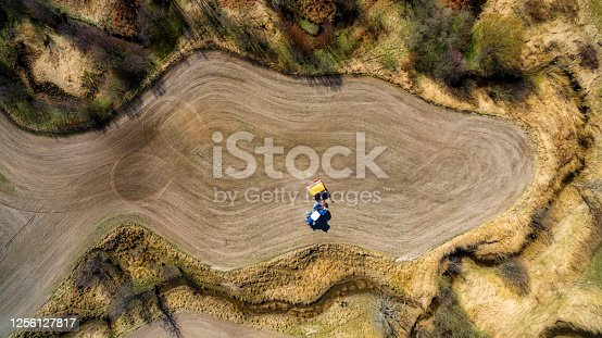 Tractor with a rotary rake leaves a trail of gathered grass, hay,  thats look like art,  air photography