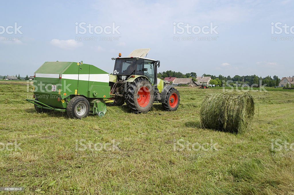 tractor bailer collect hay in agriculture field stock photo
