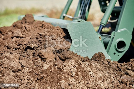 Close up of a tractor bucket shoveling a pile of dirt