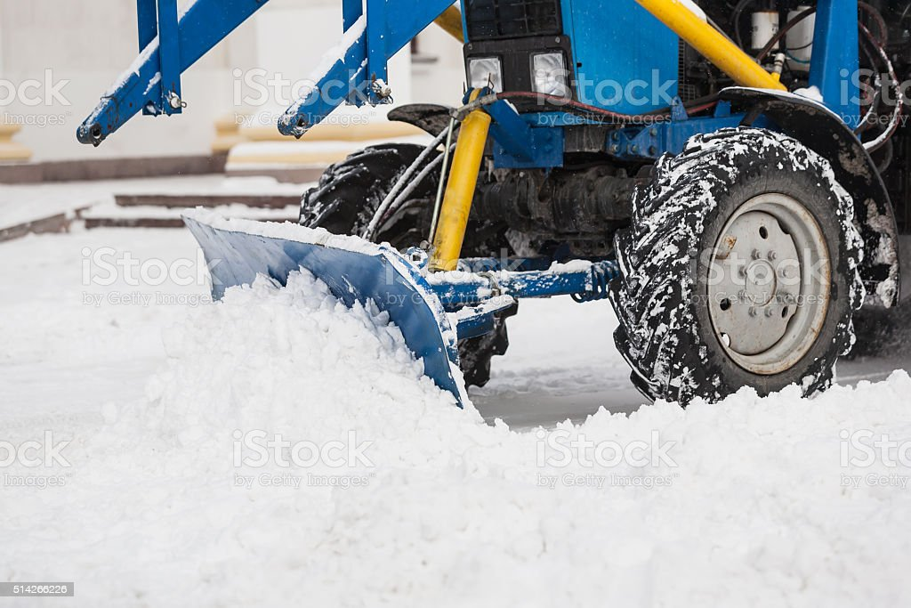 Tractor cleaning snow in city stock photo