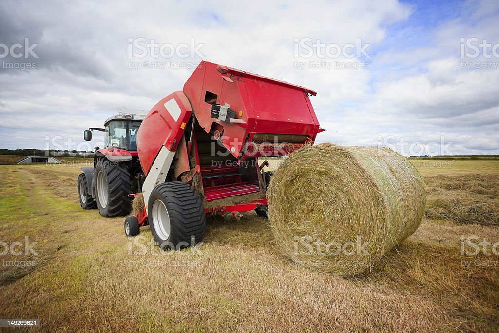 tractor collecting haystack in the field stock photo