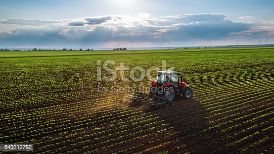 Tractor cultivating field at spring,aerial view