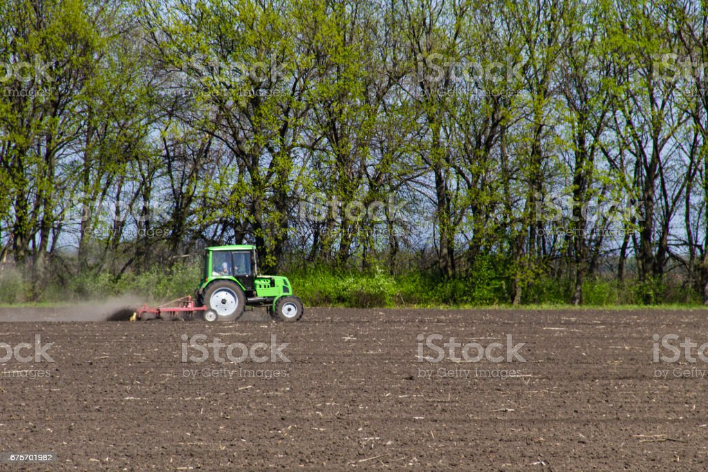 Tractor cultivating field on spring royalty-free stock photo