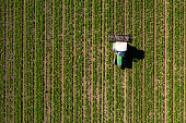 Drone shot of tractor cultivating agricultural field.