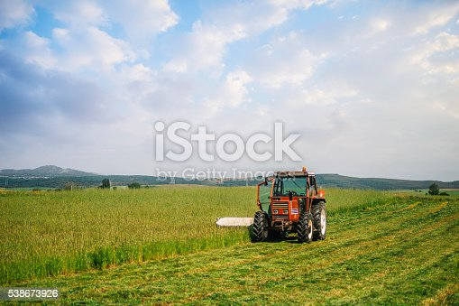 A beautiful countryside scene with a tractor cutting grass.