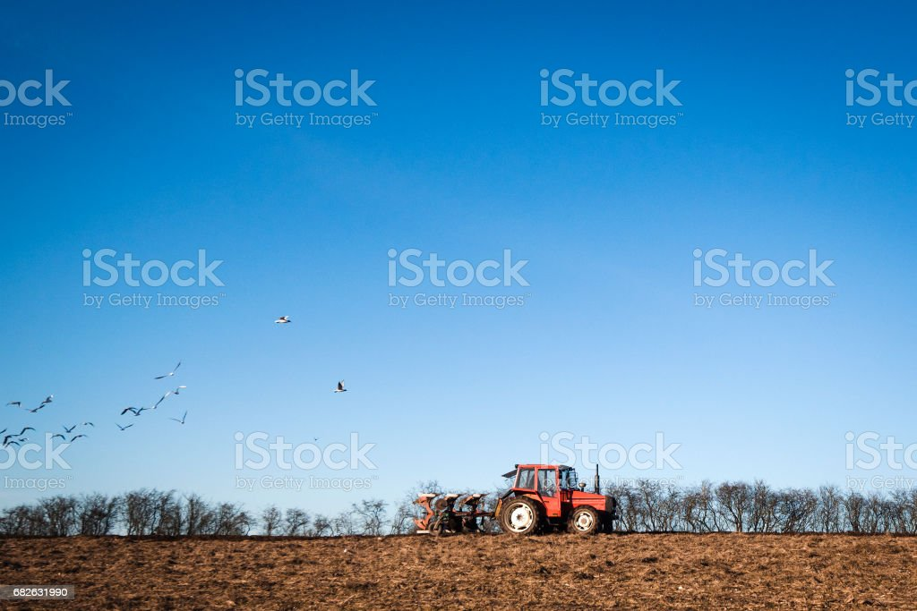 Tractor driving on a field with a plow stock photo