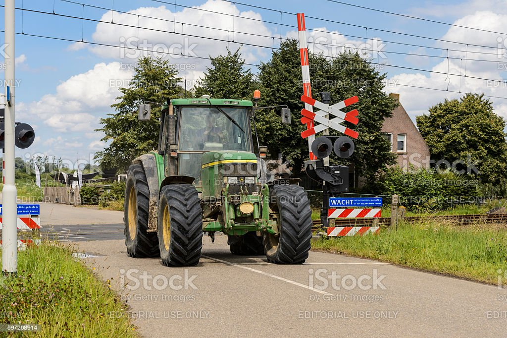 Tractor driving over railway crossing royalty-free stock photo
