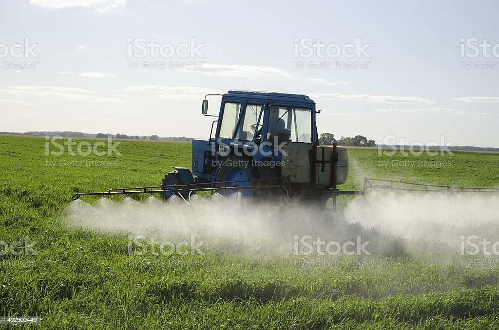 Tractor fertilize field pesticide and insecticide stock photo