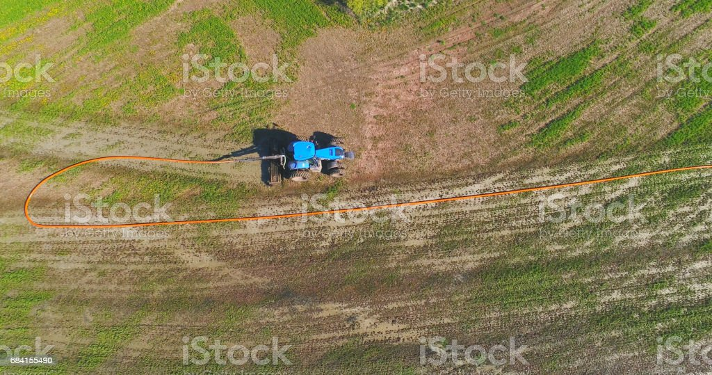 Tractor fertilizing field with liquid manure pumped from distant tanker. foto stock royalty-free