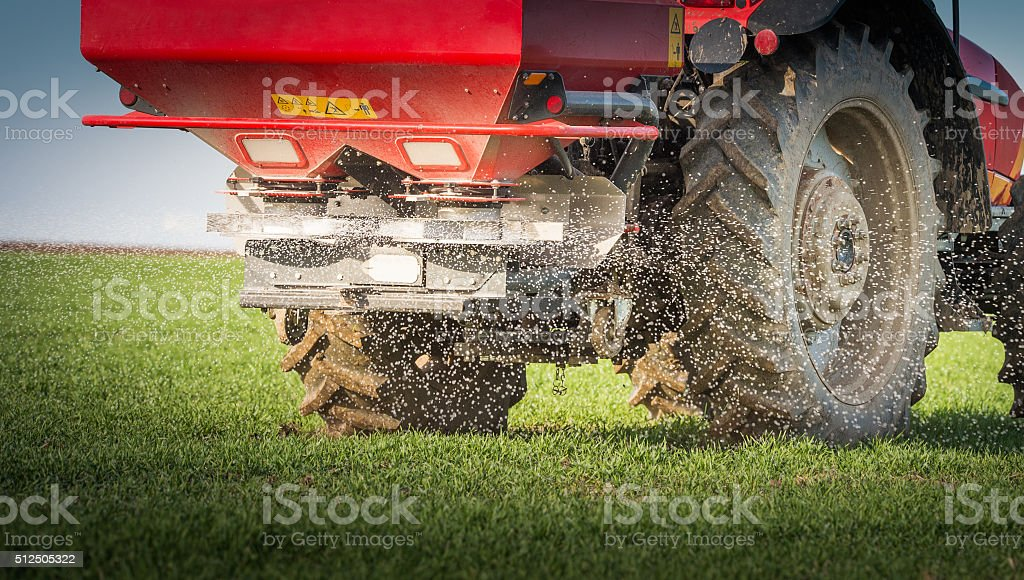 tractor fertilizing in field stock photo