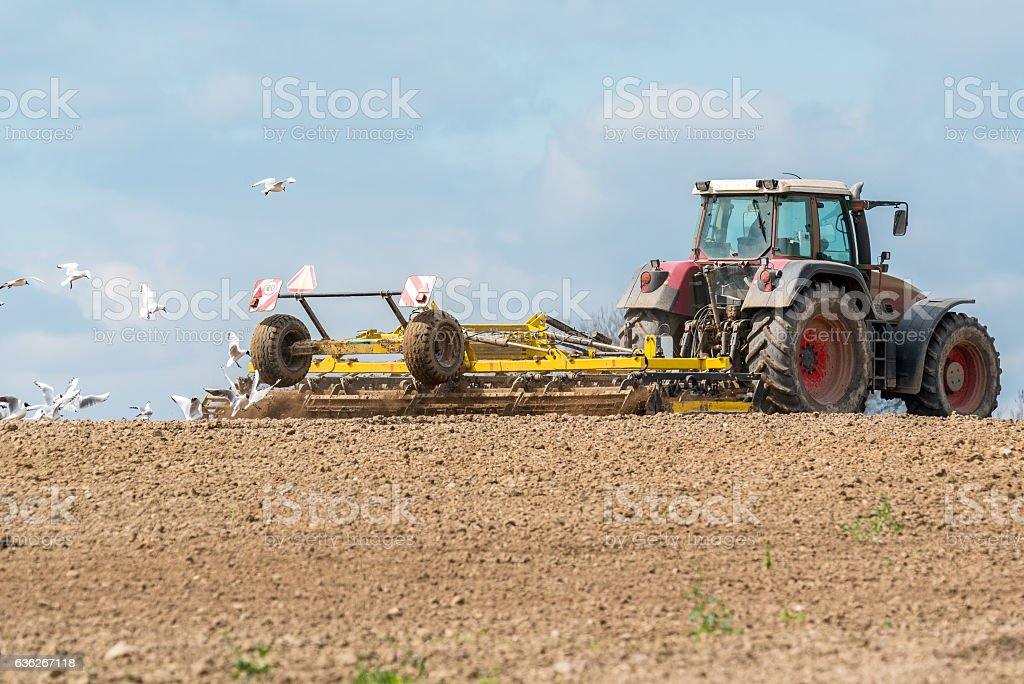 Tractor harrowing the field stock photo