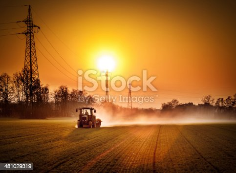 Tractor in a field at sunset. Electricity pylon in the background.